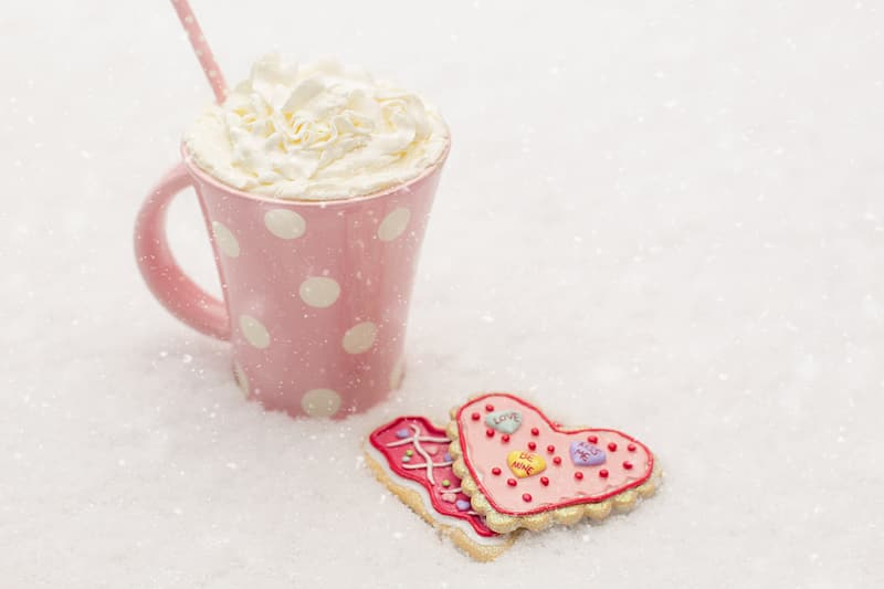 Two heart shaped cookies beside whip cream served on white and pink polka dot mug