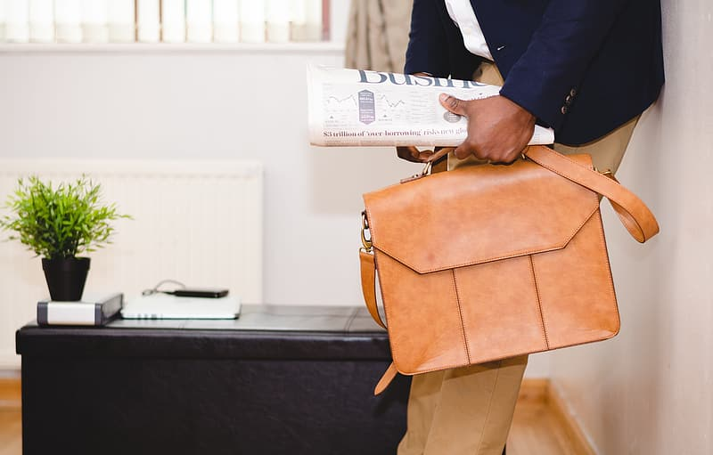 Person holding newspaper and brown leather bag