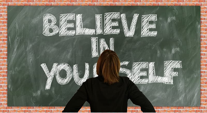 Person in black long-sleeved top facing blackboard with believe in yourself text