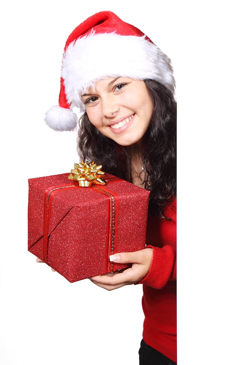Girl wearing Santa hat and holding red gift box
