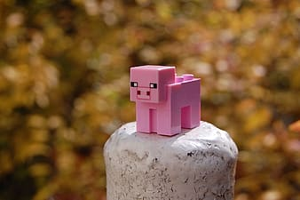 Selective focus photo of pink animal minecraft toy on rock