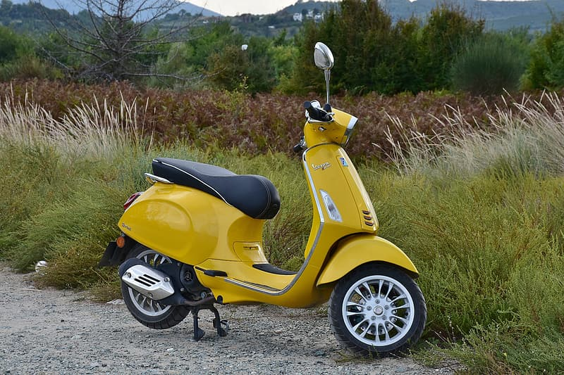 Yellow motor scooter parked near grass