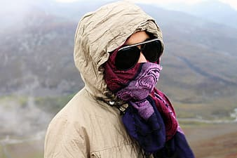 Person wearing sunglasses and overall coat