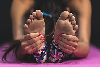 Woman holding her feet using both hands while head touching her toes