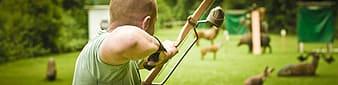 Man using composite bow aiming at animals