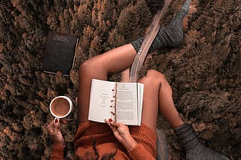 Woman wearing orange sweater and grey socks reading a book with white mug