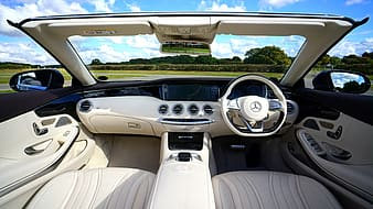 Grey and black Mercedes-Benz vehicle interior overlooking green grass field and trees under cloudy sky during daytime
