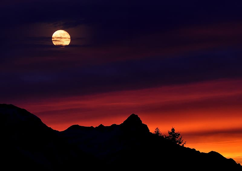 New moon over silhouette of mountain