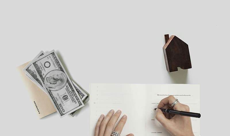 Person holding a black pen and a 100 us dollar bill