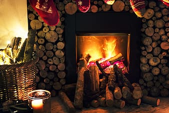 Brown and gray wooden framed fireplace surrounded with fire woods