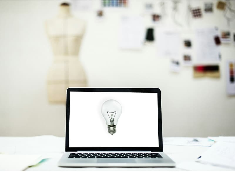 Turned-on laptop with light bulb on screen