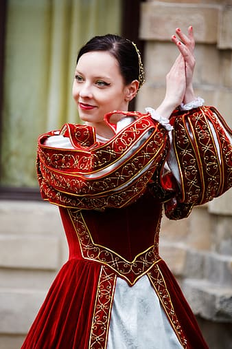 Woman wearing red and white traditional dress clapping her hands