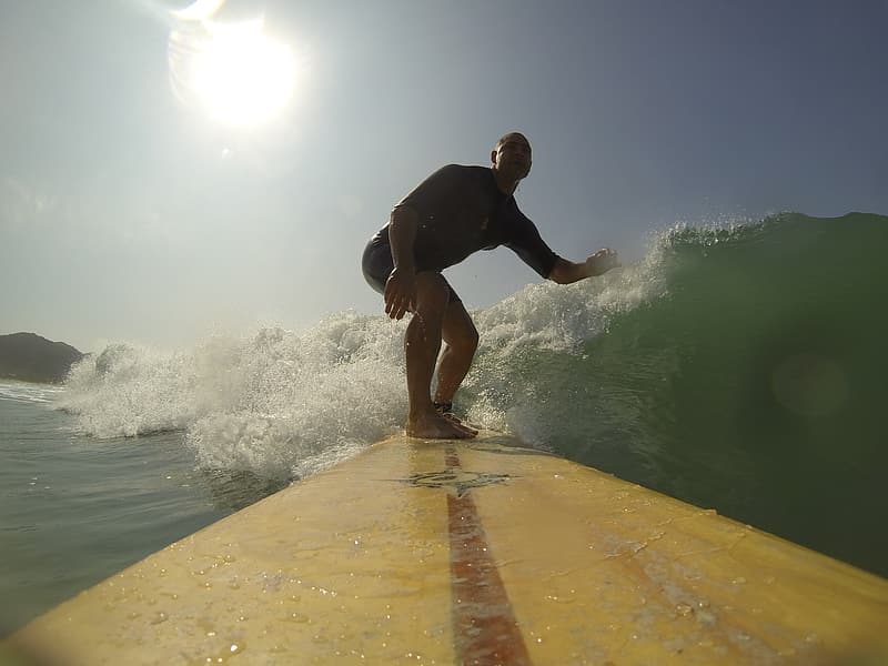 Man riding on yellow surfboard while surfing on water waves
