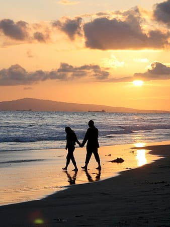Silhouette of man and woman holding hands on beach during sunset