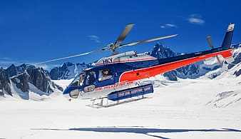 Blue and orange helicopter on snow-covered field