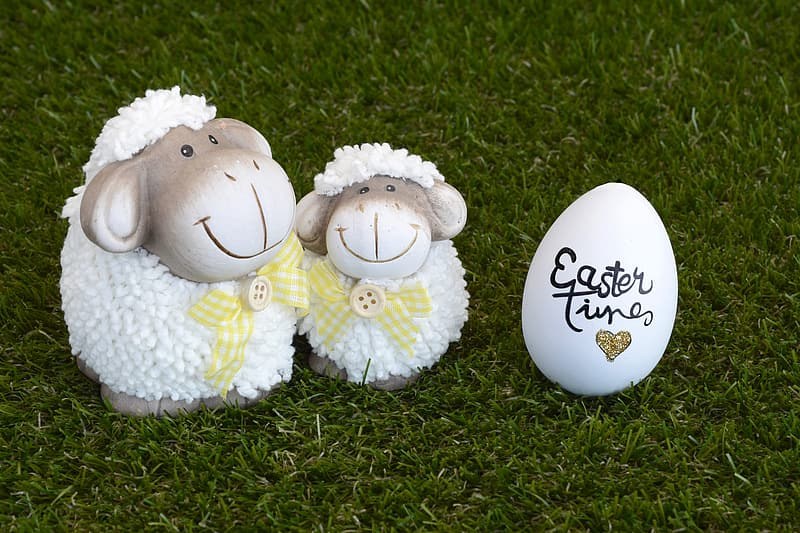 Two white lamb figurines and white egg