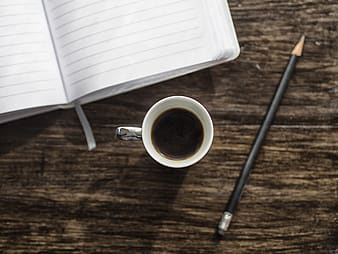 Black pencil beside mug and notebook