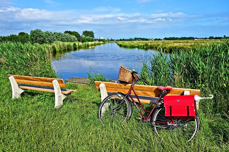 Red dutch bicycle near wooden bench during daytime