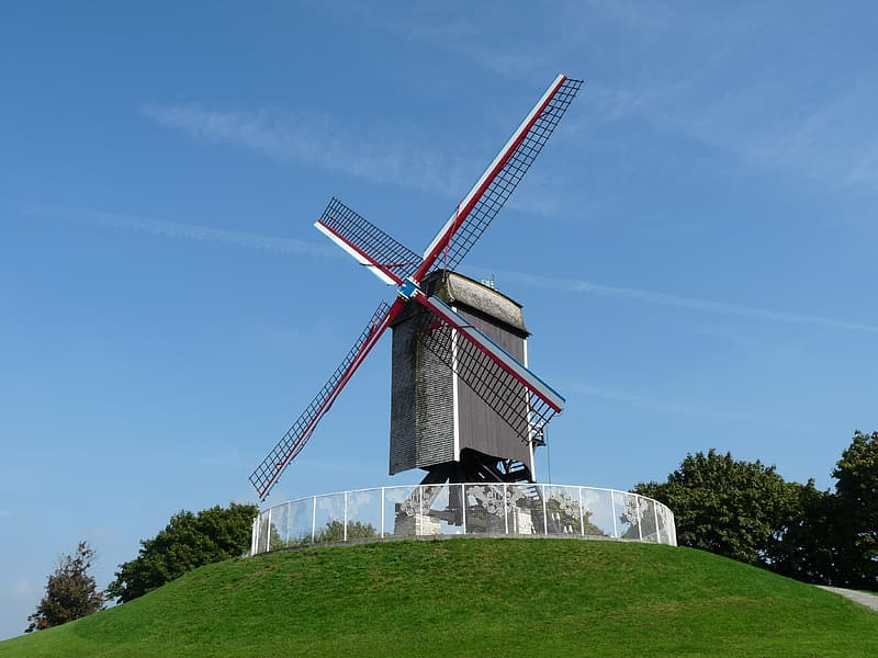 White and brown windmill on green grass field under blue sky during daytime