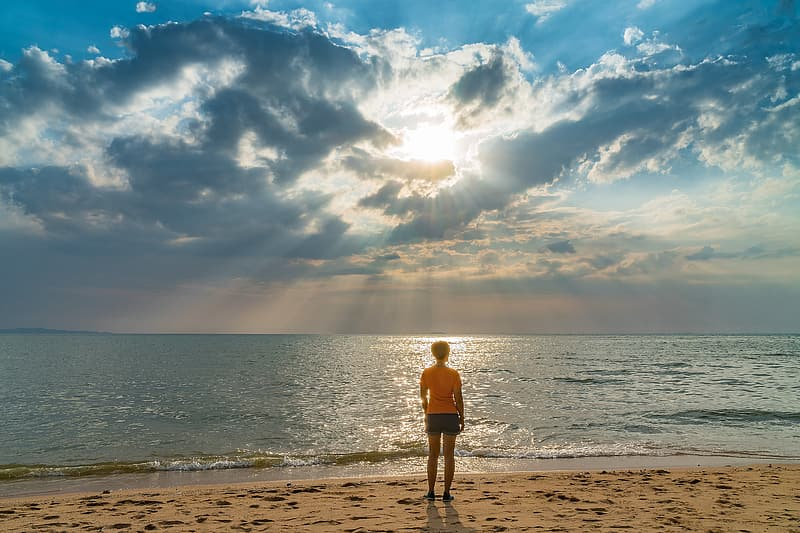 Photo of person standing seashore facing ocean during day time