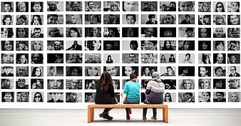 Three people sitting on bench in front of collage photos
