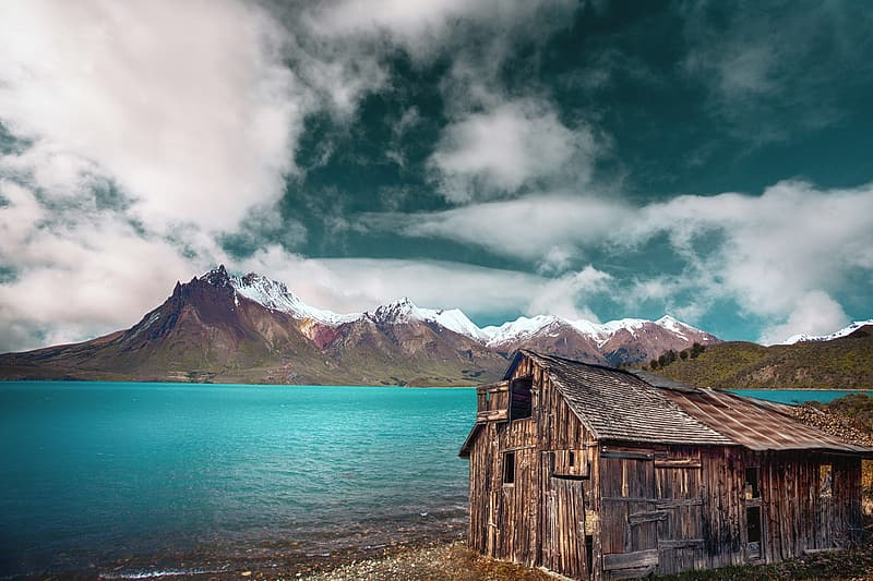 Brown wooden house near body of water under cloudy sky during daytime