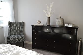 Black hemnes lowboy dresser beside gray and black padded wing chair
