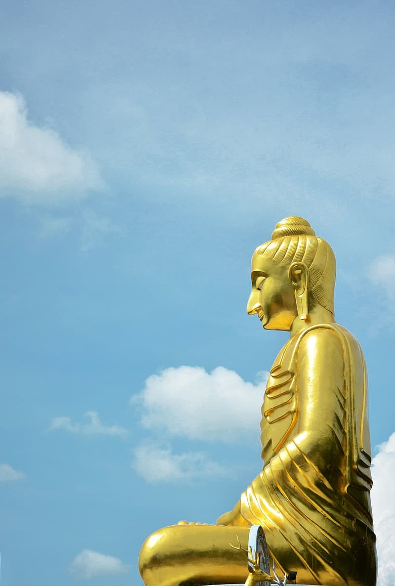 Gold-colored sitting Buddha statue under white clouded blue sky at daytime