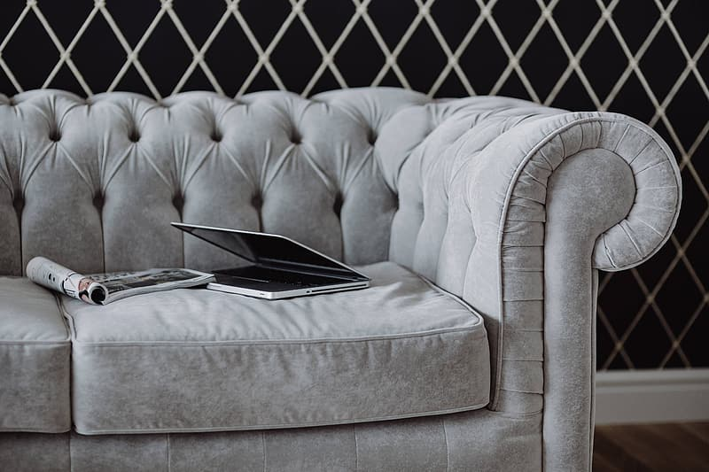 Elegant grey sofa with a laptop, an iPhone and a magazine