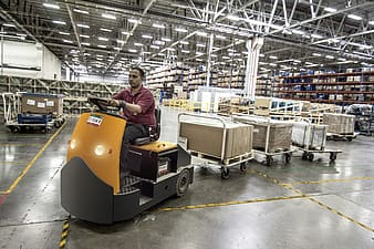 Man driving cart with boxes inside building