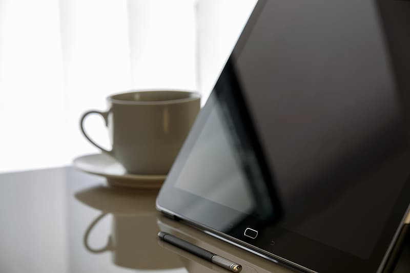 Black Samsung Galaxy tablet beside white ceramic cup