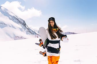 Woman holding snowboards during winter season