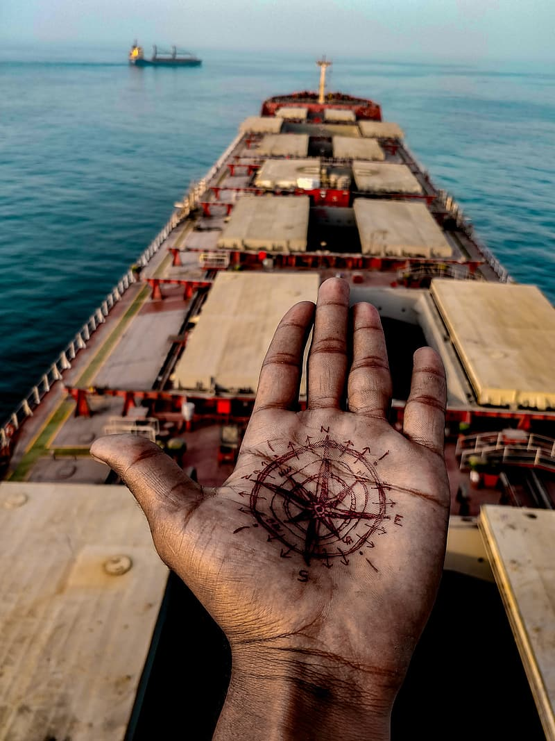 Persons hand on brown wooden dock