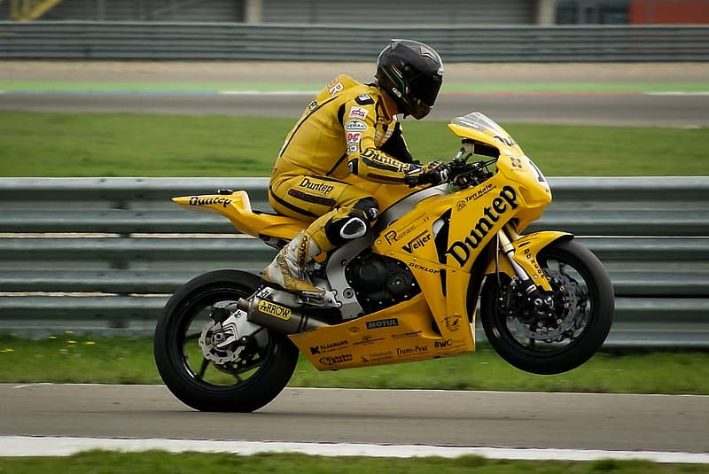 Man in yellow jacket riding yellow and black sports bike