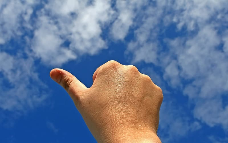Right human hand under blue sky