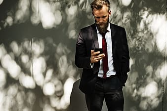 Photo of man wearing black suit jacket with dress pants and white dress shirt holding phone