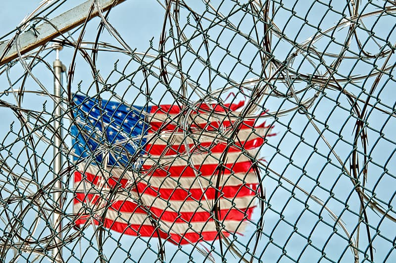 American flag beside gray wire link fence with live wire fence at daytime