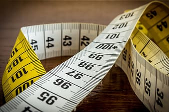 Closeup photo of yellow and white measuring tape