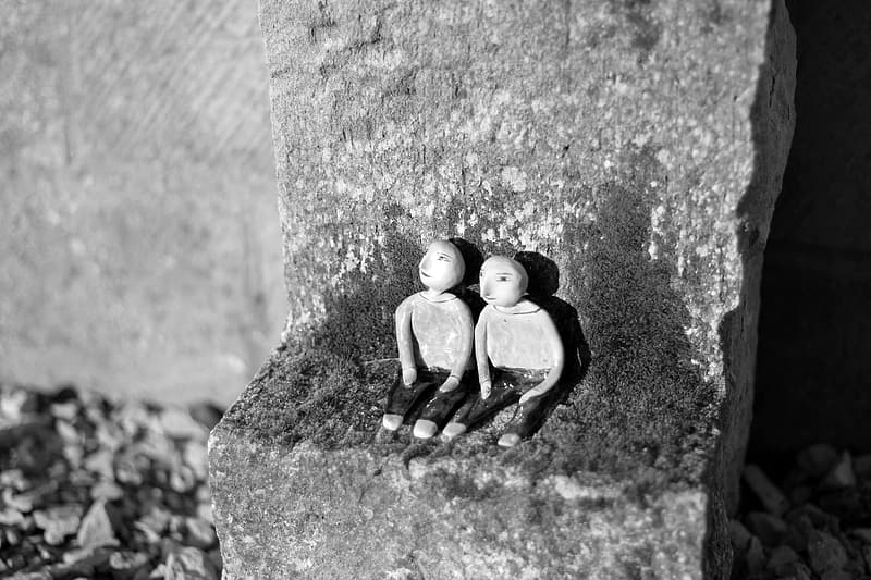 Two figurines sitting on gray stone