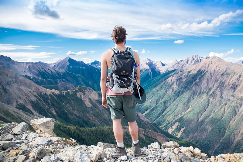 Photo of man standing on top of mountains during day time