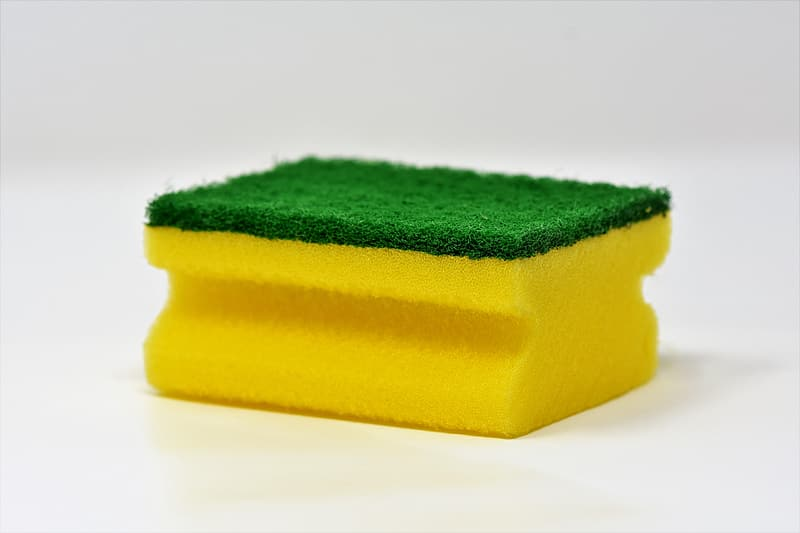 Yellow and green sponge on white surface