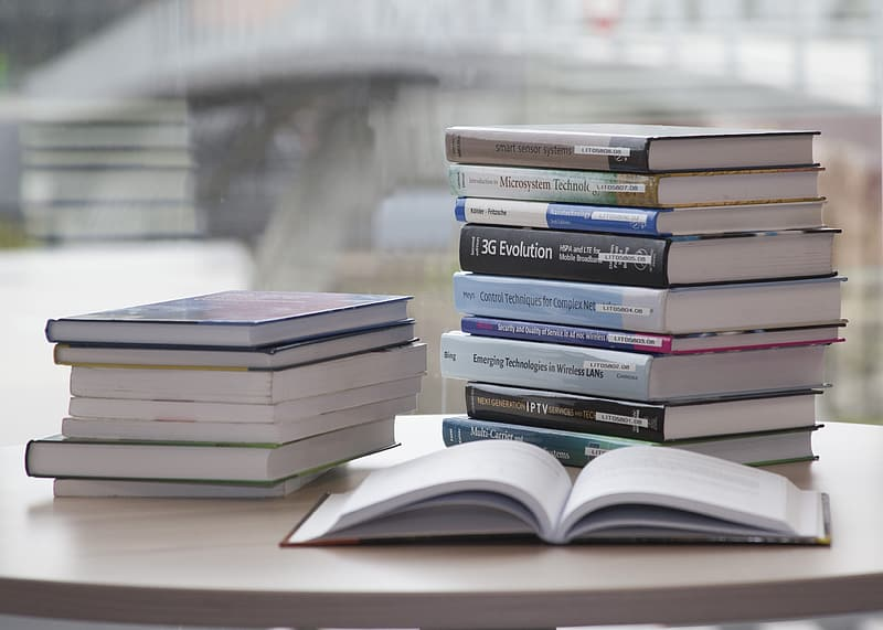 One open book beside pile of books on white table