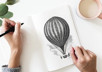 Person drawing a hot air balloon on a illustration pad
