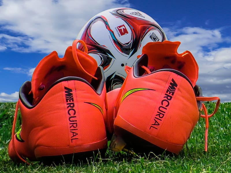 Red Nike Mercurial cleats and white and red soccer ball on ground