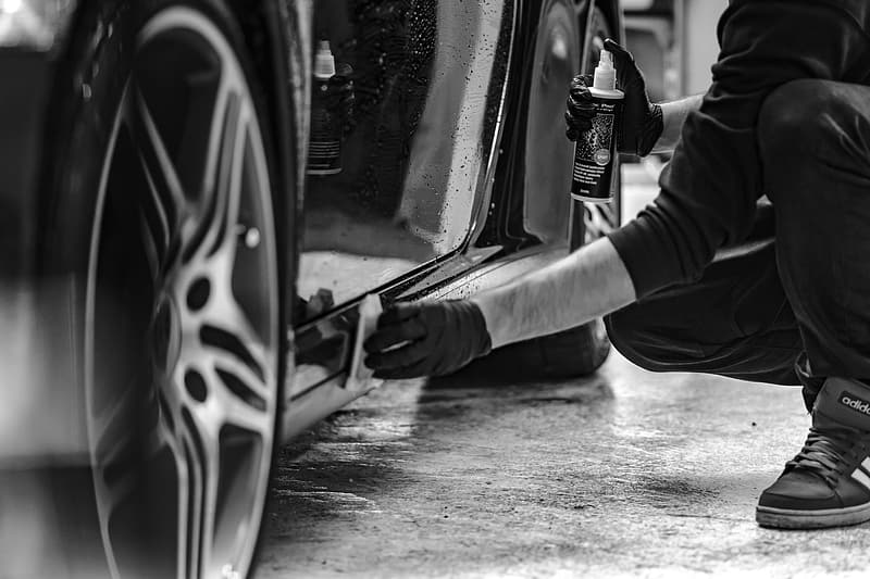 Grayscale photography of man cleaning side skirts of car