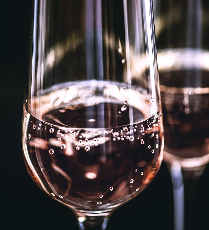 Two clear champagne glasses with brown carbonated beverage