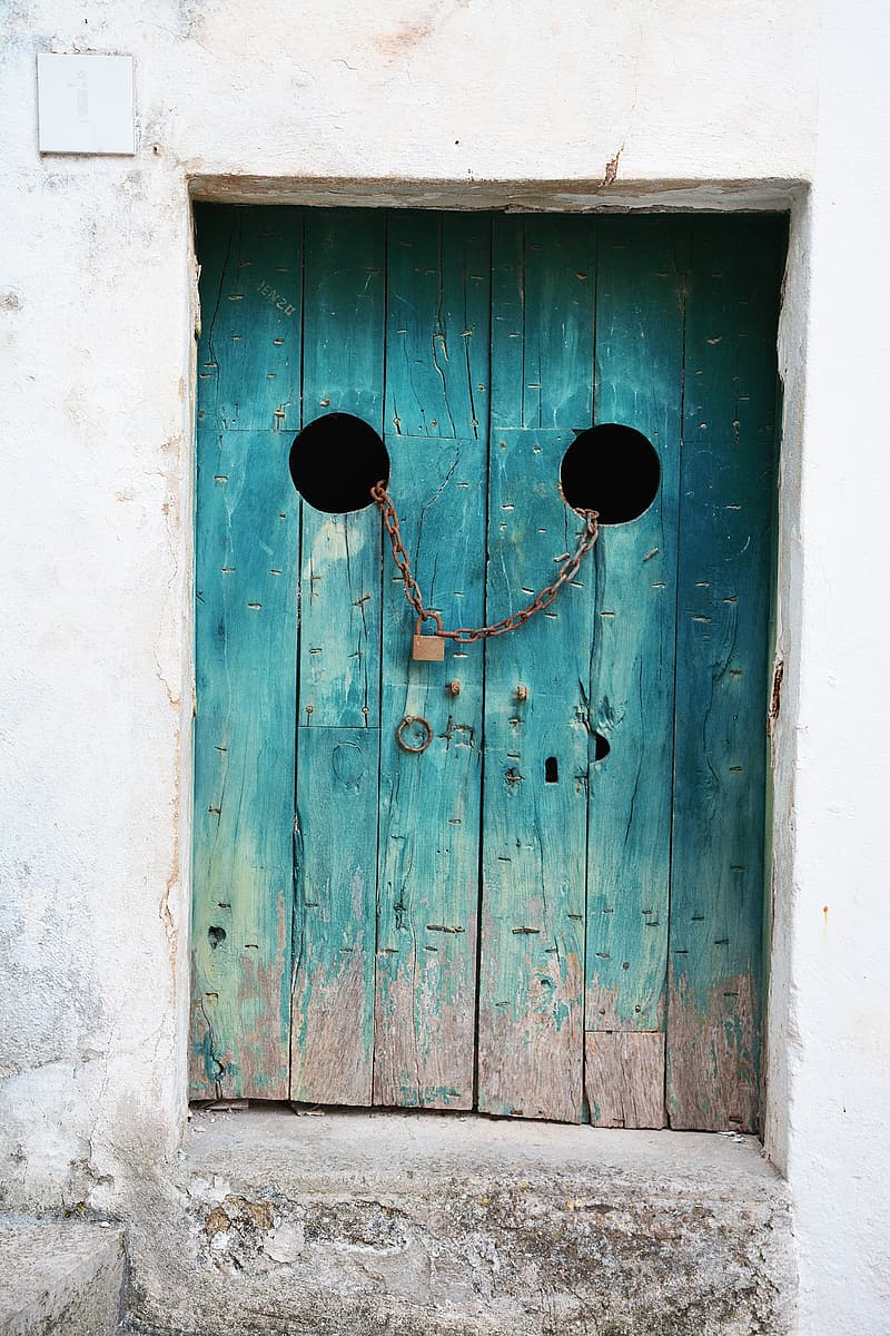 Teal wooden door with chain and padlock