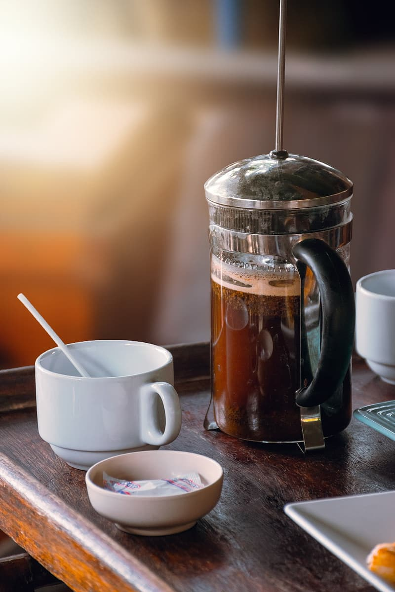 Full filled coffee press beside coffee cup on brown wooden table