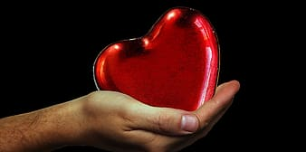 Person holding heart-shaped red case