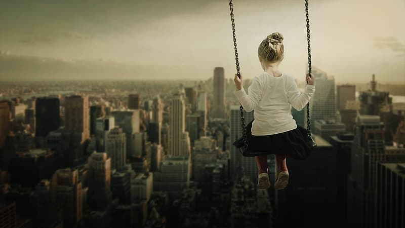 Girl sitting on swing with overlooking skycrapers